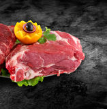 Fresh raw pork neck meat decorated with vegetables on kitchen table plus clipping path.  Stock Images