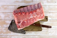 Fresh raw pork piece on wooden board. With rustic metal butcher. Food photography Stock Photos
