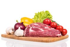 Fresh raw pork. Raw pork with spices and vegetables on the chopping board over white background Stock Photography