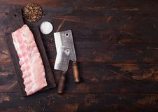 Fresh raw pork ribs on chopping board and vintage hatchets on wooden background. Pepper and salt. Space for text. Fresh raw pork ribs on chopping board and stock photos