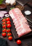 Fresh raw pork ribs on chopping board and vintage meat fork and knife on wooden background. Fresh tomatoes and red onion with. Garlic, salt and pepper and stock images