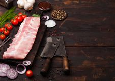 Fresh raw pork ribs on chopping board and vintage meat hatchets on wooden background. Fresh tomatoes and red onion with garlic. Salt and pepper royalty free stock photo