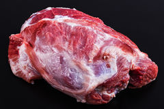 Fresh raw pork shoulder on black background. View from above, close-up Royalty Free Stock Photo