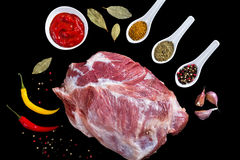 Fresh raw pork shoulder with ingredients for marinade. Black, green, pink and white peppercorns, dried herbs, chili, bay leaf, garlic, barbecue sauce Stock Photography