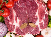 Fresh raw pork. Raw pork with spices and fresh bright vegetables Royalty Free Stock Image