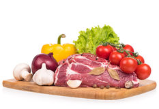 Fresh raw pork. Raw pork with spices and vegetables on the chopping board over white background Royalty Free Stock Photos