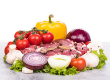 Fresh raw pork. Raw pork with spices and vegetables on the chopping board over white background Royalty Free Stock Photo