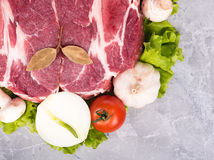 Fresh raw pork. Raw pork with spices and vegetables over the table-top background Stock Image