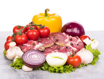 Fresh raw pork. Raw pork with spices and vegetables on the table-top over white background Stock Images