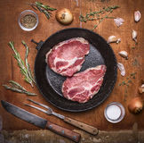 Fresh raw pork steak on a cast iron frying pan with a knife for meat fork meat onion garlic herbs and spices. wooden rustic bac Stock Image