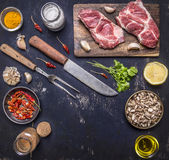 Fresh raw pork steak on a cutting board with a knife and fork for the meat with hot red peppers, lemon butter on wooden rustic. Fresh raw pork steak on a cutting Royalty Free Stock Images