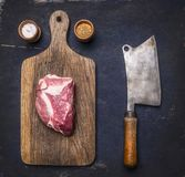 Fresh raw pork steak on a cutting board with vintage meat cleaver on a dark wooden background with pepper , salt. Fresh raw pork steak on a cutting board with Royalty Free Stock Photo