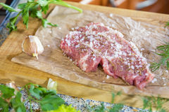Fresh raw pork steak on paper. Fresh raw pork steak with salt and spices on paper. Fresh green dill and parsley.  Shallow depth of field. Coloring and processing Royalty Free Stock Images
