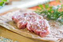 Fresh raw pork steak on paper. Fresh raw pork steak with salt and spices on paper. Fresh green dill and parsley.  Shallow depth of field. Coloring and processing Royalty Free Stock Image