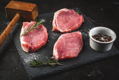 Fresh raw pork, steaks. On a cutting shale board on a black concrete table. Close view, with hammer to beat meat, copy space Stock Image