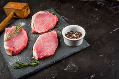 Fresh raw pork, steaks. On a cutting shale board on a black concrete table. Close view, with hammer to beat meat, copy space Stock Photos
