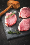 Fresh raw pork, steaks. On a cutting shale board on a black concrete table. Close view, with hammer to beat meat, copy space, vertical Royalty Free Stock Photo