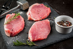 Fresh raw pork, steaks. On a cutting shale board on a black concrete table. Close view, with a hammer to beat the meat and a fork, copy space Royalty Free Stock Images