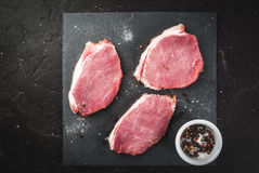 Fresh raw pork, steaks. On a cutting shale board on a black concrete table. Top view, copy space Royalty Free Stock Photos