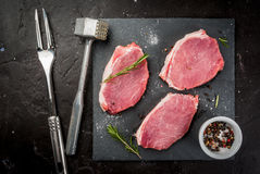 Fresh raw pork, steaks. On a cutting shale board on a black concrete table. Top view, with a hammer to beat the meat and a fork, copy space Royalty Free Stock Images