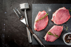 Fresh raw pork, steaks. On a cutting shale board on a black concrete table. Top view, with a hammer to beat the meat and a fork, copy space Royalty Free Stock Photos