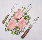 Fresh raw pork steaks with herbs, a knife and fork for the meat on the grill for roasting wooden rustic background top view Royalty Free Stock Images