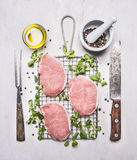 Fresh raw pork steaks with herbs, a knife and fork for the meat on the grill for roasting wooden rustic background top view. Fresh raw pork steaks with herbs, a Royalty Free Stock Image