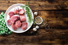 Fresh raw pork tenderloin, chopped meat on dark wooden rustic background. Top view Royalty Free Stock Photography