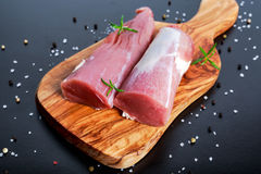 Fresh Raw pork tenderloin on wooden board .ready to cook.  Royalty Free Stock Photography