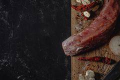 Fresh raw pork tenderloin on wooden cutting board on dark background and blank space for your text stock photography