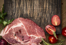 Fresh raw pork with tomatoes and onions on cutting board on wooden rustic background top view close up. Fresh raw pork with tomatoes and onions  cutting board on Stock Photography