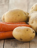 Fresh raw potato and carrot on wood Stock Photography