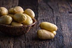 Fresh raw potatoes in basket on rustic oak board Stock Image