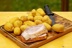 Fresh raw potatoes with meat and knife on wooden table.  Royalty Free Stock Image
