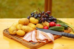 Fresh raw potatoes with meat and vegetables and knife on wooden table. Fresh raw potatoes and vegetables with meat and knife on wooden table Royalty Free Stock Image