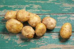 Fresh raw potatoes. On a old green wooden background Stock Photos