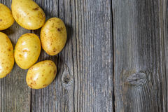 Raw potatoes in an old sack on wooden background. Free place for text. Top view Royalty Free Stock Images