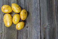 Raw potatoes in an old sack on wooden background. Free place for text. Top view Stock Image