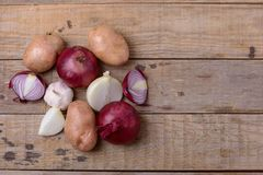 Fresh raw potatoes and onion on wooden background Royalty Free Stock Image