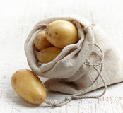 Fresh raw potatoes. On white wooden table Stock Images