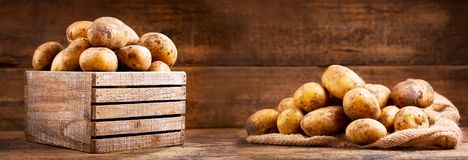 Fresh raw potatoes in a wooden box. On wooden background Royalty Free Stock Photo