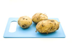 Fresh Raw Potatos. On blue underlay Royalty Free Stock Photography