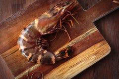 Fresh raw prawns. Delicious fresh prawn on wooden chopping board Royalty Free Stock Images