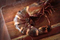 Fresh raw prawns. Delicious fresh prawn on wooden chopping board Royalty Free Stock Photos