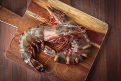 Fresh raw prawns. Delicious fresh prawns on wooden chopping board Royalty Free Stock Photos