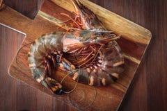 Fresh raw prawns. Delicious fresh prawns on wooden chopping board Royalty Free Stock Image