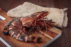Fresh raw prawns. Delicious fresh prawns on wooden chopping board Stock Images