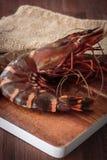 Fresh raw prawns. Delicious fresh prawns on wooden chopping board Royalty Free Stock Photography