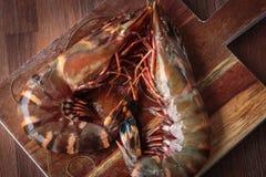 Fresh raw prawns. Delicious fresh prawns on wooden chopping board Stock Photos
