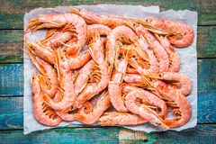 Fresh raw prawns on paper. On a rustic wooden table Royalty Free Stock Image